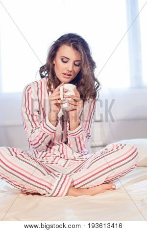 girl in pajamas woke up in the morning is sitting on a bed and drink coffee or tea
