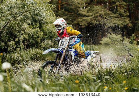 Kyshtym Russia - June 18 2017: motorcycle crosses puddles of water and mud in forest during Ural Cup in Enduro