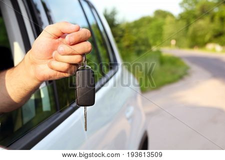 car keys in the male hand out of the car window in sunny summer day. rent or buy car concept.