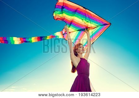 Beauty girl holding colorful kite on summer field with colorful air balloons over blue clear sky. Happy young healthy woman enjoying nature outdoors. Running and Spinning female. Flying