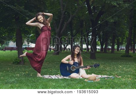 Young boho hippie girls dance with guitar in park. Friendship and fun