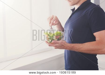 Man eat healthy lunch in modern interior. Unrecognizable profile male torso in blue t-shirt, hand with fork, near window with vegetable salad in bowl, diet food concept. High key image