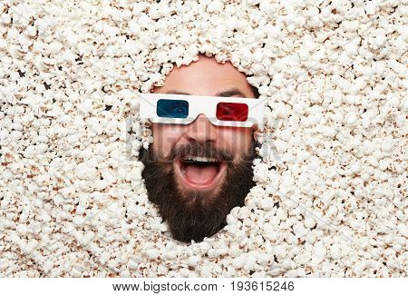 From above shot of bearded man wearing stereo glasses lying in popcorn and looking excitedly at camera.