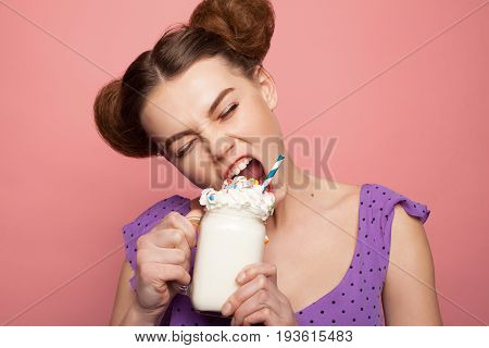 Girl with fancy hairdo holding jar filled with whip and trying to eat it in expressive manner.