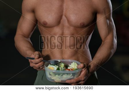 Close up of man athlete with vegetables. Proper nutrition concept. Healthy eating and sport right lifestyle choice