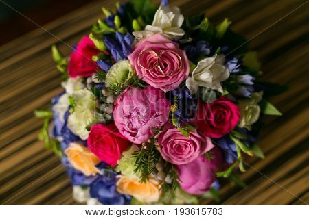 wedding bouquet of peonies and roses with wedding rings.