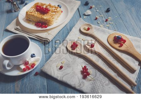 Pastry pie and berries - cowberry, red currant and bluberries. Beautiful food served at blue rustic wooden table, cake dessert at ethnic porcelain plate, tea and coffee cup.
