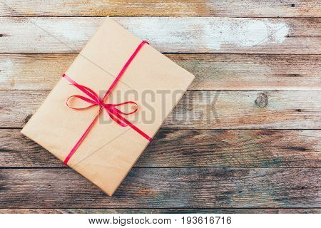 a gift in wrapping paper and tied with a red ribbon on wooden retro grunge background top view closeup