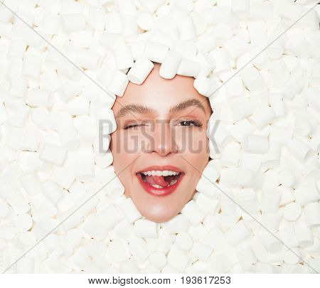 From above view of young female face winking at camera and lying in white marshmallows.