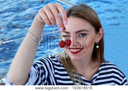 Attractive young woman coquettish eats cherry. dressed in a sailor suit. Sunny day. Summer style. Stripes.