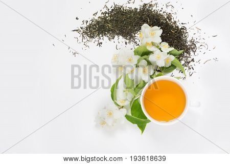 Jasmine dry green tea leaves with jasmine flowers and cup of tea on white background.