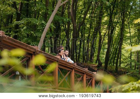 Young interracial family standing on wooden bridge in forest