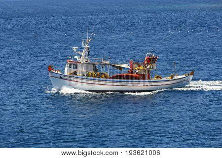 ADAMANTAS, GREECE - MAY 23, 2017: Traditional fishing boat in the open sea near Adamantas village, Milos island on May 23, 2017.