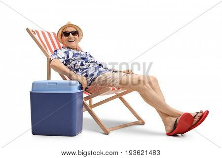 Elderly man sitting in a deck chair next to a cooling box isolated on white background