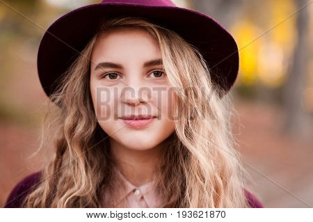 Closeup portrait of teen blonde girl 14-16 year old wearing hat outdoors over autumn background. Walking in park. Smiling teenager.