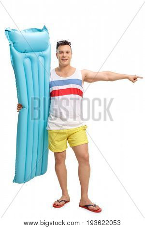 Full length portrait of a tourist holding an air mattress and pointing right isolated on white background