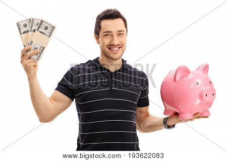 Young man holding bundles of money and a piggybank isolated on white background