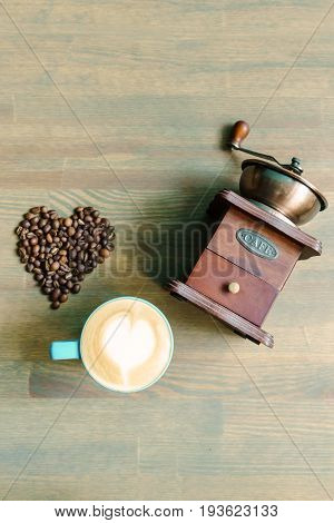 A Cup Of Cappuccino, Coffee Grinder And Heart Of Beans On Wooden Table