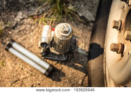 Pneumatic car jack next to old tire. Auto mobile repair objects concept.