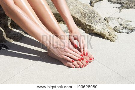 Pretty woman feet with red manicure and pedicure: relaxing on sand. Holiday, vacation, spa, summer: concept.