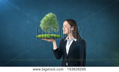 Portrait Of Young Woman Holding Green Tree On The Open Hand Palm, Over Isolated Studio Background. B