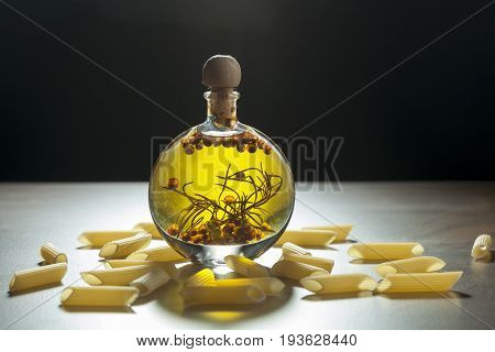 Bottle Extra Virgin Olive Oil With Spices And Some Pieces Of Pasta On A Ceramic Background