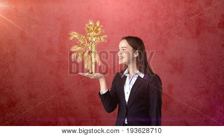Portrait Of Young Woman Holding Golden Palm On The Open Hand Palm, Over Isolated Studio Background.