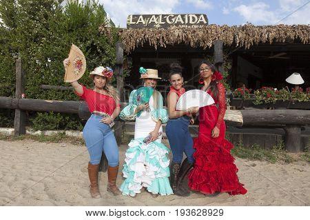 El Rocio Spain - June 2 2017: Group of young female pilgrims in traditional flamenco dresses in El Rocio during the pilgrimage Romeria 2017. Province of Huelva Andalusia Spain