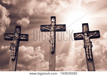 Crucifixion of Jesus Christ and the two thieves. Public sculpture at the cemetery. With sunlight and clouds background.