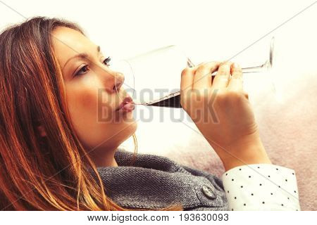 Alcoholism, woman drinking glass red wine. A beautiful woman is in the home and is drinking a glass of red wine. Alcoholism concept female, but also to relax, drink, social or party event.