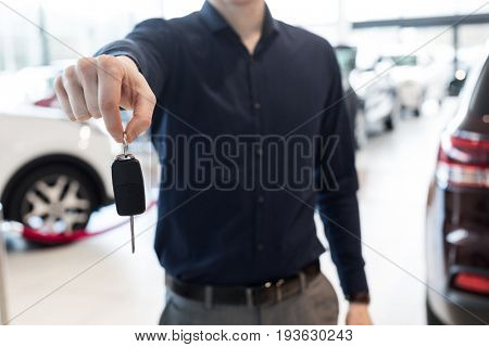 Midsection of salesman showing car keys while standing in showroom