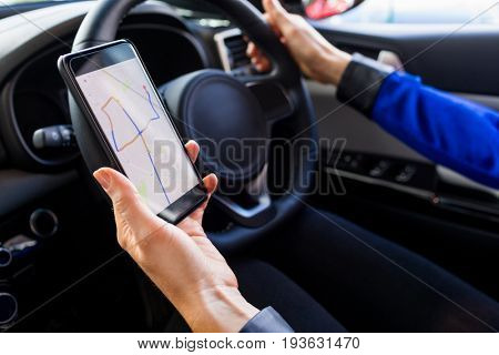 Cropped image of woman using smartphone during test drive in car at showroom