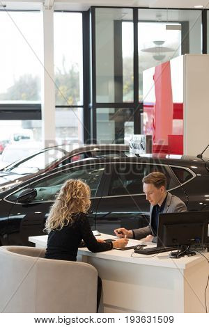 Female customer discussing with salesman while sitting at desk in carshowroom