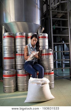 Female worker writing on clipboard while sitting by kegs in factory