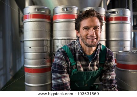 Portrait of smiling male worker sitting by kegs at warehouse