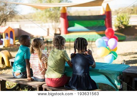 Rear view of children sitting on bench at park