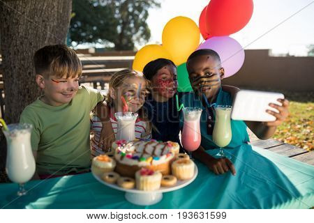 Boy taking selfie with friends while sitting by food and drink at park