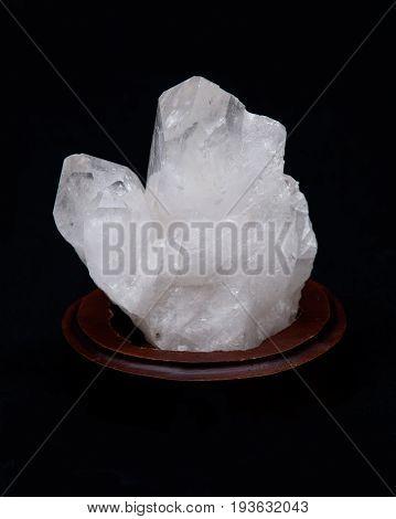 Clear quartz cluster on black fabric background