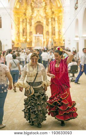 El Rocio Spain - June 2 2017: Pilgrims in traditional spanish flamenco dress in the hermitage of El Rocio during the Romeria 2017. Andalusia Spain