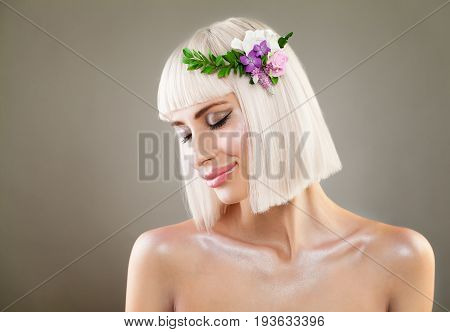 Pretty Blonde Girl Smiling. Nice Fashion Model with Bob Hairstyle and Flowers