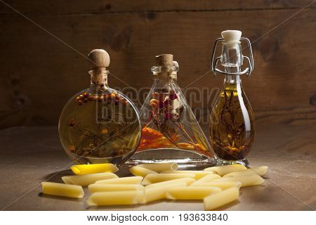 Bottles Extra Virgin Olive Oil With Spices And Some Pieces Of Pasta On A Ceramic Background