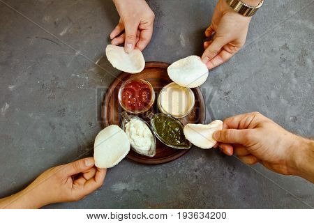 Beautiful Fresh Rice Chips With Sauce On A Wooden Board In The Hands Of Women And Men