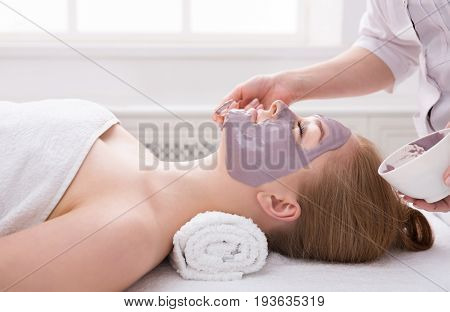 Apply clay face mask, spa beauty treatment and skincare. Woman getting facial nourishing mask by beautician at spa salon, close-up