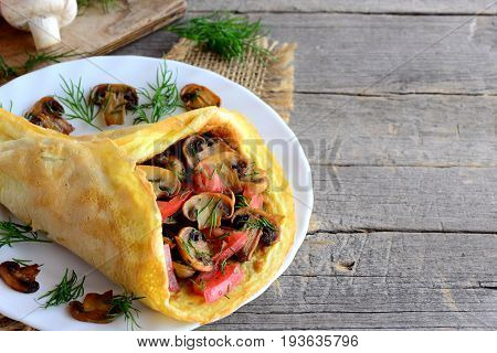 Yummy omelette stuffed with fried mushrooms, fresh tomato slices and dill. Home stuffed omelette on a plate and on a vintage wooden background with copy space for text. Rustic style