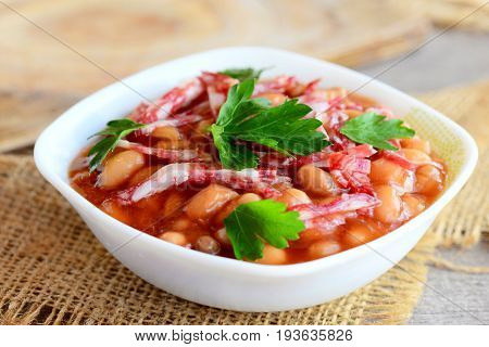 Smoked sausages with white beans in tomato sauce. Simple white bean and smoked sausage stew in a white bowl and on a wooden old table. Home nutritious stew. Closeup