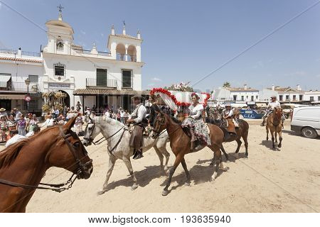 El Rocio Spain - June 2 2017: Pilgrims on horseback in traditional spanish dress in El Rocio during the Romeria 2017. Province of Huelva Almonte Andalusia Spain