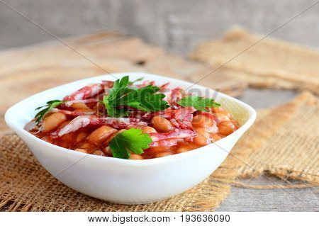 Smoked sausages with white beans in classic tomato sauce. Tasty white beans and smoked sausage stew in a white bowl and on a burlap textile. Rustic style. Home stew