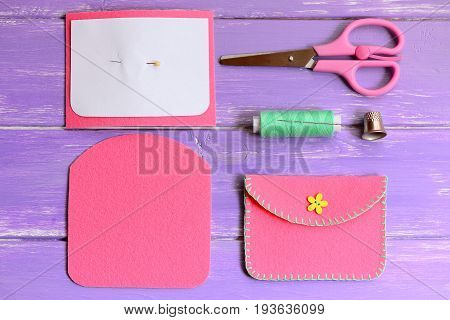 Pink felt purse with yellow flower button. Scissors, thread, needle, thimble, paper template, felt pieces on a wooden table. Simple handmade crafts for kids. Top view