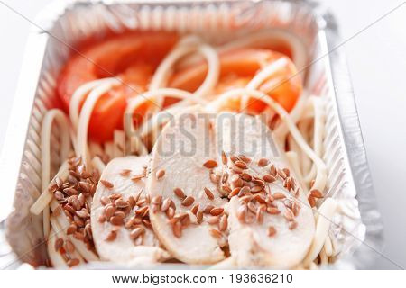 Healthy lunch in foil container. Fitness menu take away and delivery. Durum wheat pasta, steamed turkey, fresh vegetables and flax seeds in box on white background, closeup