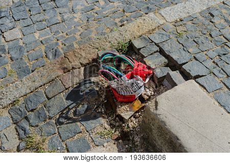 Exposed and unprotected electrical wiring on a cobbled pavement or street